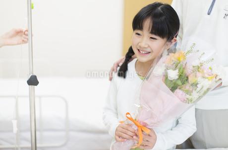 お見舞いにきて花束を渡す女の子の写真素材 [FYI02971805]