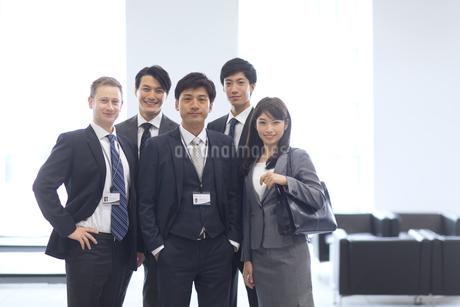 オフィスビルのロビーで立つビジネス男女の写真素材 [FYI02971818]