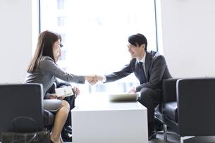 オフィスビルのロビーで握手をするビジネス男女の写真素材 [FYI02971823]