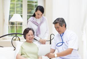 タブレットPCで説明する医者と話を聞く母と娘の写真素材 [FYI02971832]