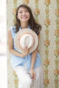 壁に寄り掛かって帽子持って笑う女性の写真素材 [FYI02971833]