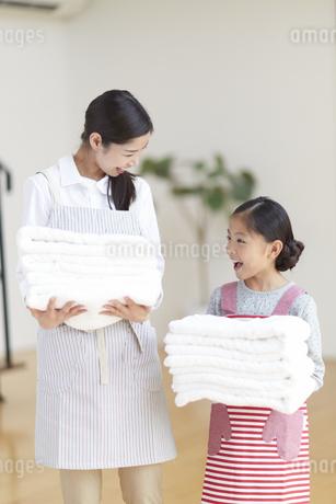 たたんだタオルを持って笑い合う親子の写真素材 [FYI02971848]