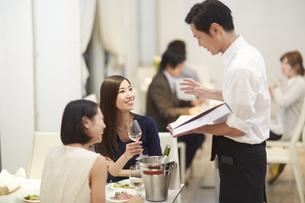 レストランで店員の話を聞く女性二人の写真素材 [FYI02971852]