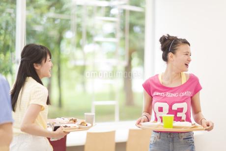 学食で笑いながらお膳を運ぶ女子学生たちの写真素材 [FYI02971864]