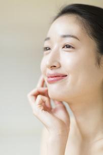 頬に片手を添えて微笑む女性の写真素材 [FYI02971868]