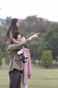 公園で指を差しながら遠くを見る家族の写真素材 [FYI02971870]