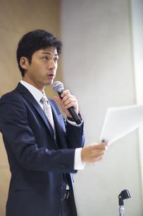 マイクを手に講義するビジネス男性の写真素材 [FYI02971874]