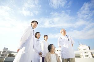 屋上で車椅子の患者に添う医師たちの写真素材 [FYI02971877]