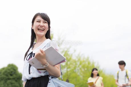 新緑を背景に歩く女子学生の写真素材 [FYI02971885]