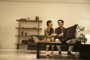 額装を手にソファーで語らう夫婦の写真素材 [FYI02971891]