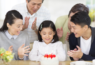 ケーキを前に誕生日のお祝いをする家族の写真素材 [FYI02971893]