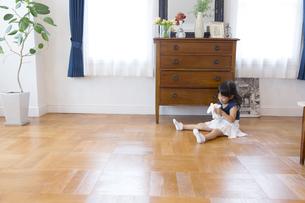 床に座ってぬいぐるみと遊ぶ女の子の写真素材 [FYI02971898]