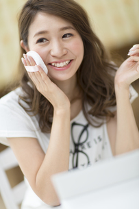鏡の前でスキンケアをする微笑む女性の写真素材 [FYI02971899]