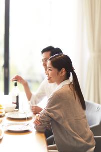 ワインと食事を前に男性と一緒に微笑む女性の写真素材 [FYI02971905]