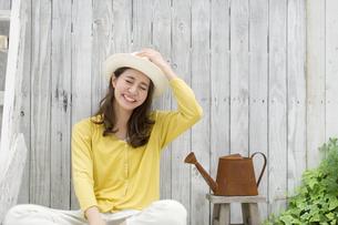 帽子を被ってテラスでくつろぐ女性の写真素材 [FYI02971909]