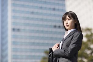 ビルを背景に上を見るビジネス女性の写真素材 [FYI02971912]
