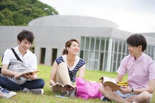 芝に座り談笑する学生たちの写真素材 [FYI02971914]