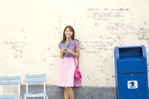 壁に寄り掛かってスマートフォンを持つ女性の写真素材 [FYI02971931]