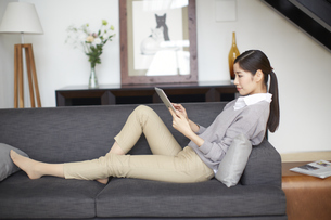 ソファーでスマートデバイスを見る女性の写真素材 [FYI02971932]