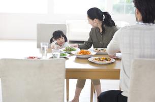 ダイニングテーブルで食事を楽しむ親子の写真素材 [FYI02971933]