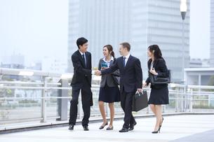 オフィスビルを背景に歩きながら握手を交わすビジネス男女の写真素材 [FYI02971935]