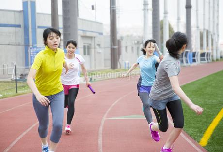 陸上競技場でバトンの手渡しをする女子学生たちの写真素材 [FYI02971937]