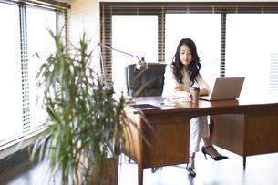 オフィスのデスクに座るビジネス女性の写真素材 [FYI02971941]