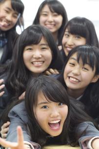 教室の席の上で重なって笑う女子高校生たちの写真素材 [FYI02971945]