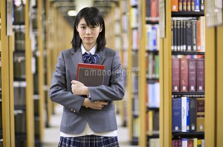 図書室で本を抱える女子高校生の写真素材 [FYI02971948]