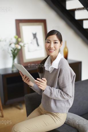 ソファーでスマートデバイスを持つ女性のスナップの写真素材 [FYI02971952]