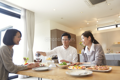 食事を囲んで会話する女性とワインを注ぐ男性の写真素材 [FYI02971953]