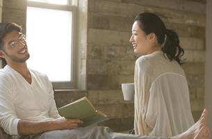 ベッドの上で談笑する男性と女性の写真素材 [FYI02971954]