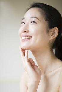 顎に片手を添えて上を見上げ微笑む女性の写真素材 [FYI02971963]