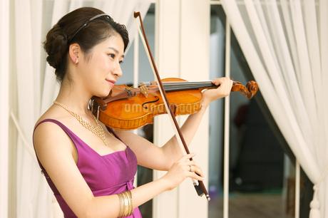 ドレスアップしてバイオリンを弾く女性の写真素材 [FYI02971980]