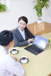 説明する訪問営業の女性と話を聞く男性の写真素材 [FYI02971997]