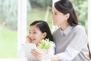 タブレットPCを持つ母と笑顔の女の子の写真素材 [FYI02971999]