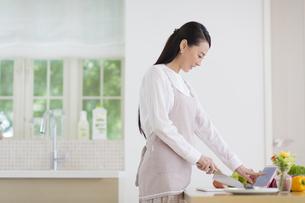 キッチンでタブレットPCを見る奥さんの写真素材 [FYI02972003]