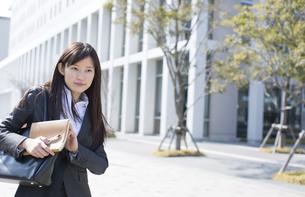 手帳を手に前を見つめるビジネス女性の写真素材 [FYI02972006]