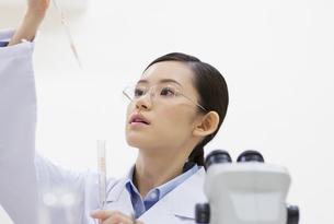 ピペットを使って計量している女性研究員の写真素材 [FYI02972010]