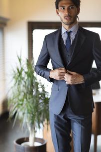 オフィスでスーツのジャケットを整えるビジネス男性の写真素材 [FYI02972011]