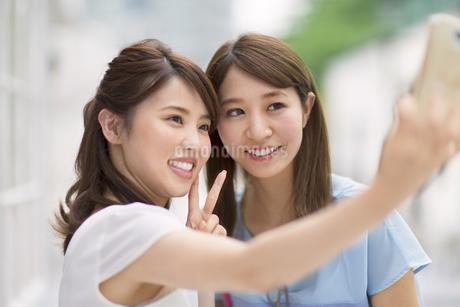 スマートフォンで写真を撮る2人の女性の写真素材 [FYI02972014]