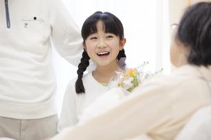 お見舞いにきて花束を渡す女の子の写真素材 [FYI02972018]