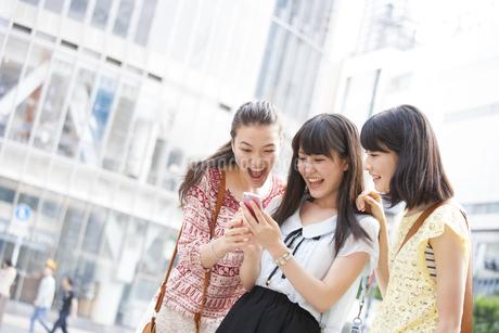 スマートフォンを見つめて喜ぶ3人の若い女性の写真素材 [FYI02972020]