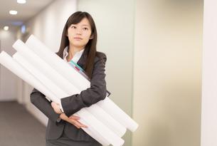 筒を抱えて廊下を歩くビジネス女性の写真素材 [FYI02972022]