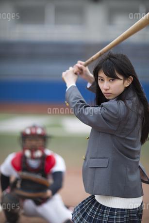野球バットを持って打つ構えをする女子学生の写真素材 [FYI02972028]
