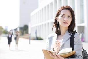 手帳を手にカメラ目線のビジネス女性の写真素材 [FYI02972035]