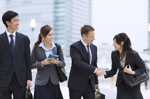 オフィスビルを背景に歩きながら握手を交わすビジネス男女の写真素材 [FYI02972038]