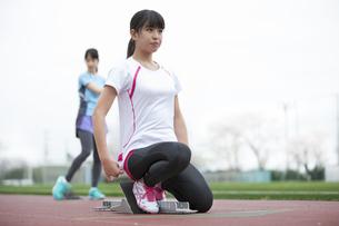 リレーのスタートの準備運動をする女子学生の写真素材 [FYI02972041]