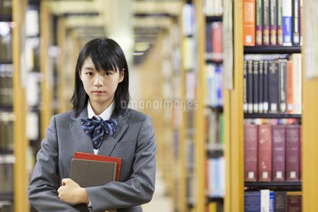 図書室で本を抱える女子高校生の写真素材 [FYI02972045]