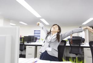 デスクで伸びをするビジネス女性の写真素材 [FYI02972047]